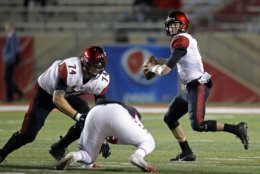 San Diego State quarterback Ryan Agnew, right, throws as offensive lineman Tyler Roemer (74) contains a New Mexico defender during the first half of an NCAA college football game in Albuquerque, N.M., Saturday, Nov. 3, 2018. (AP Photo/Andres Leighton)