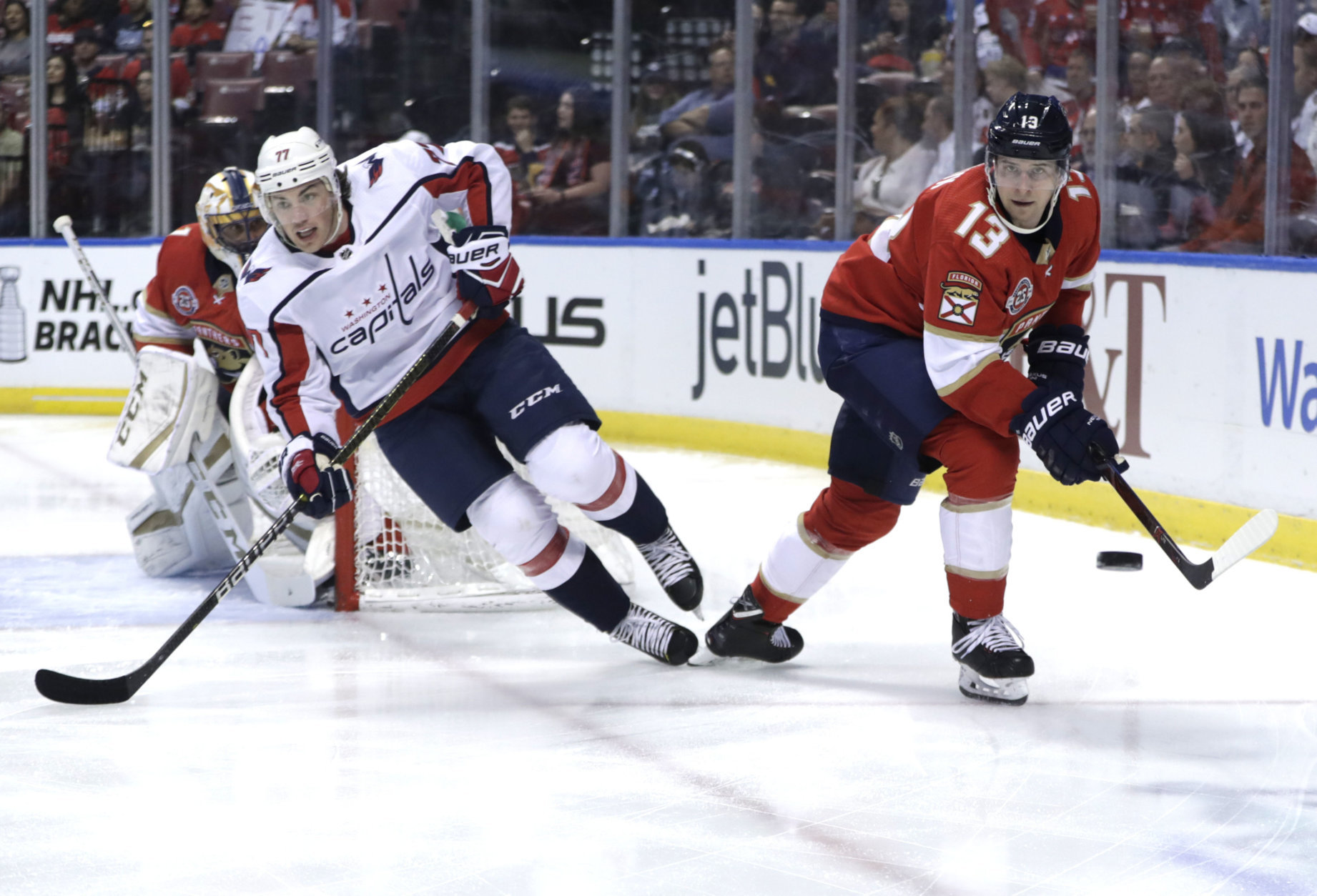 Florida Panthers defenseman Mark Pysyk (13) skates with the puck as Washington Capitals right wing T.J. Oshie (77) defends during the first period of an NHL hockey game, Monday, April 1, 2019, in Sunrise, Fla. (AP Photo/Lynne Sladky)