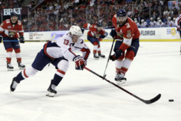 Washington Capitals left wing Jakub Vrana (13) skates with the puck as Florida Panthers defenseman Keith Yandle (3) pursues during the first period of an NHL hockey game, Monday, April 1, 2019, in Sunrise, Fla. (AP Photo/Lynne Sladky)