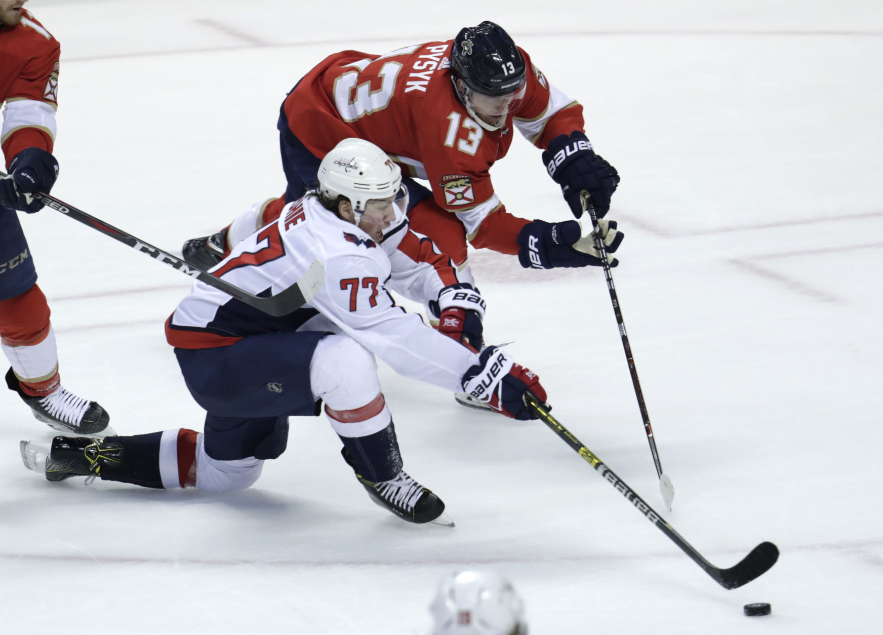 Washington Capitals right wing T.J. Oshie (77) and Florida Panthers defenseman Mark Pysyk (13) go for the puck during the third period of an NHL hockey game, Monday, April 1, 2019, in Sunrise, Fla. (AP Photo/Lynne Sladky)