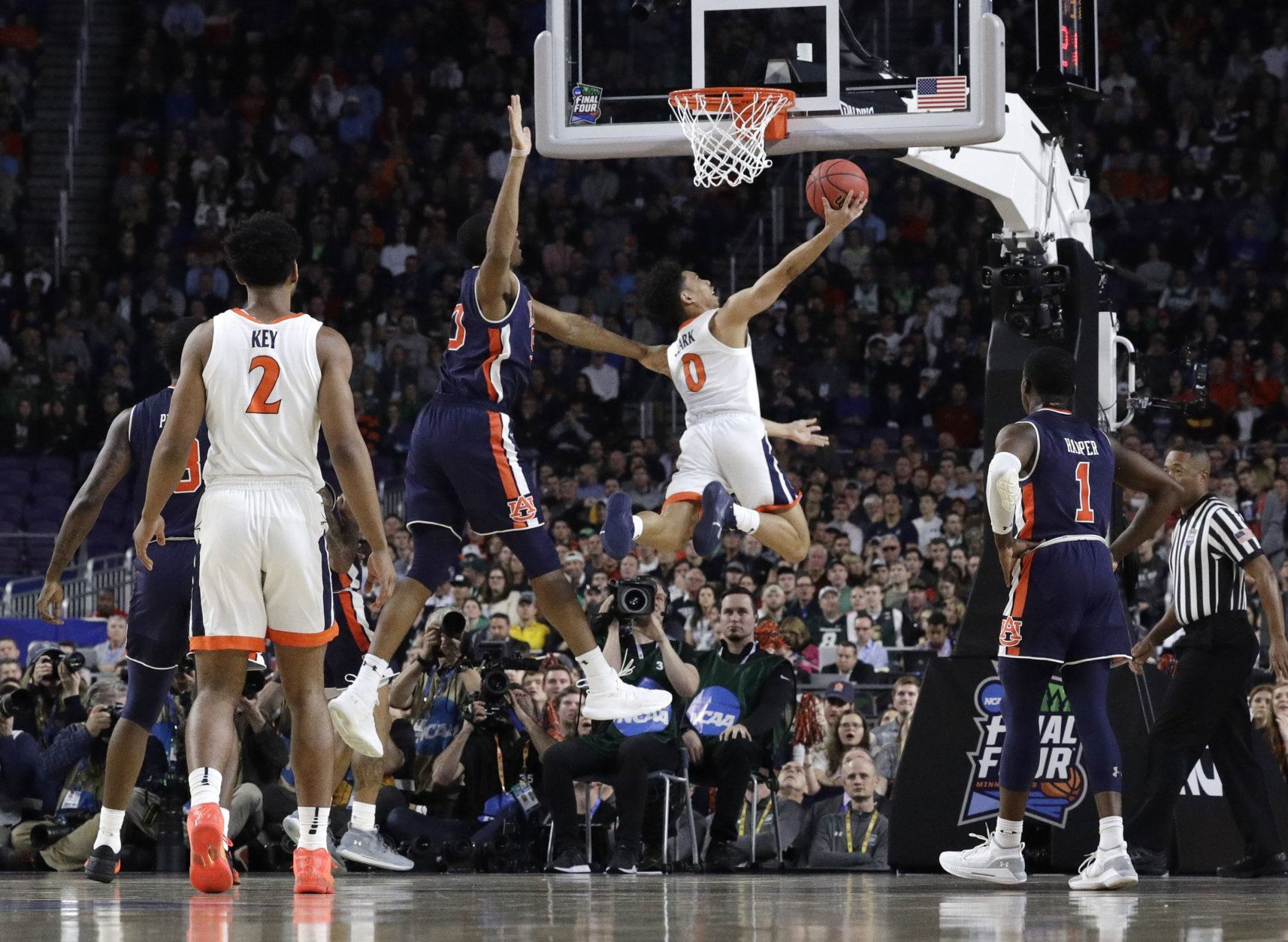 Virginia guard Kihei Clark (0) drives to the basket past Auburn center Austin Wiley during the first half in the semifinals of the Final Four NCAA college basketball tournament, Saturday, April 6, 2019, in Minneapolis. (AP Photo/David J. Phillip)