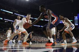 Virginia guard Kyle Guy, left, fights for a loose ball with Auburn forward Danjel Purifoy during the second half in the semifinals of the Final Four NCAA college basketball tournament, Saturday, April 6, 2019, in Minneapolis. (AP Photo/Jeff Roberson)