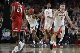 Virginia guard Kyle Guy (5) celebrates in front of Texas Tech guard Jarrett Culver (23) at the end of the championship game in the Final Four NCAA college basketball tournament, Monday, April 8, 2019, in Minneapolis. Virginia won 85-77 in overtime. (AP Photo/David J. Phillip)