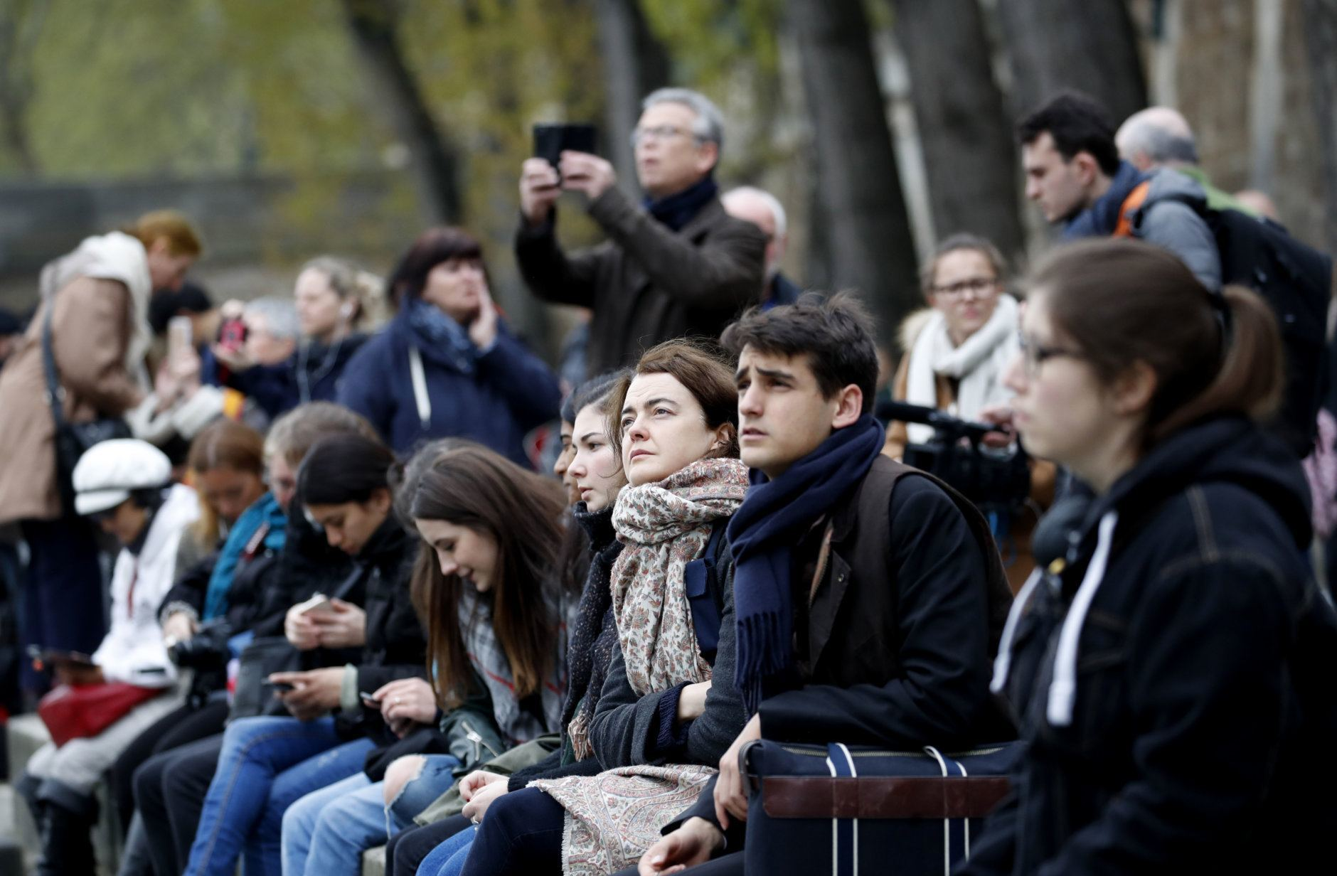 People watch and photograph the Notre Dame cathedral after the fire in Paris, Tuesday, April 16, 2019. Experts are assessing the blackened shell of Paris' iconic Notre Dame cathedral to establish next steps to save what remains after a devastating fire destroyed much of the almost 900-year-old building. With the fire that broke out Monday evening and quickly consumed the cathedral now under control, attention is turning to ensuring the structural integrity of the remaining building. (AP Photo/Christophe Ena)