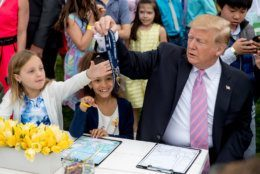 President Donald Trump gives a girl the whistle he used for the annual White House Easter Egg Roll on the South Lawn of the White House, Monday, April 22, 2019, in Washington.
