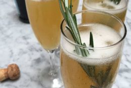 This Dec. 3, 2015, photo, shows sparkling orchard grove cocktails, which spike sparkling wine with an apple cider-orange juice reduction, amaretto liqueur and a sprig of fresh rosemary in Concord, N.H. The New Year's Eve cocktail can be prepared ahead of time. (AP Photo/J.M. Hirsch)