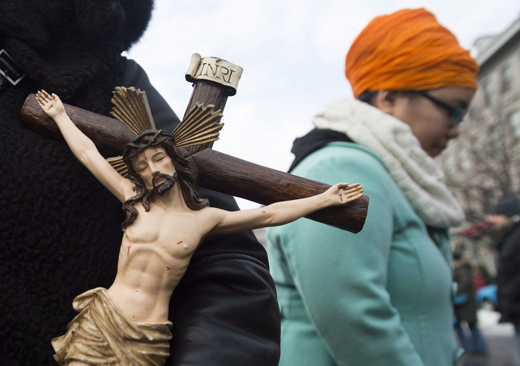 In this Sunday, Jan. 12, 2014, photo, a woman holds a crucifix during a gathering in Montreal to oppose the proposed Quebec Values Charter. A proposal to ban many public employees from wearing religious symbols, Bill 21, is creating a fiery debate in the Canadian province of Quebec. Bill 21 is Quebec's fourth legislative attempt since 2011 to regulate the wearing of religious symbols for people working in the public sphere, and for the first time it invokes a constitutional clause allowing local governments to override some constitutional rights. (Graham Hughes/The Canadian Press via AP)
