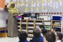 In this Thursday, April 4, 2019, photo, kindergarten teacher Haniyfa Scott gives a lesson during class in Montreal. The Quebec government's recently tabled Bill 21 bans the wearing of religious symbols for new government placed employees within schools, the courts and law enforcement. Bill 21 is Quebec's fourth legislative attempt since 2011 to regulate the wearing of religious symbols for people working in the public sphere, and for the first time it invokes a constitutional clause allowing local governments to override some constitutional rights. (Graham Hughes/The Canadian Press via AP)