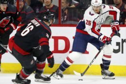 Washington Capitals' Nic Dowd (26) moves the puck as Carolina Hurricanes' Patrick Brown (36) defends during the first period of Game 4 of an NHL hockey first-round playoff series in Raleigh, N.C, Thursday, April 18, 2019, (AP Photo/Karl B DeBlaker)