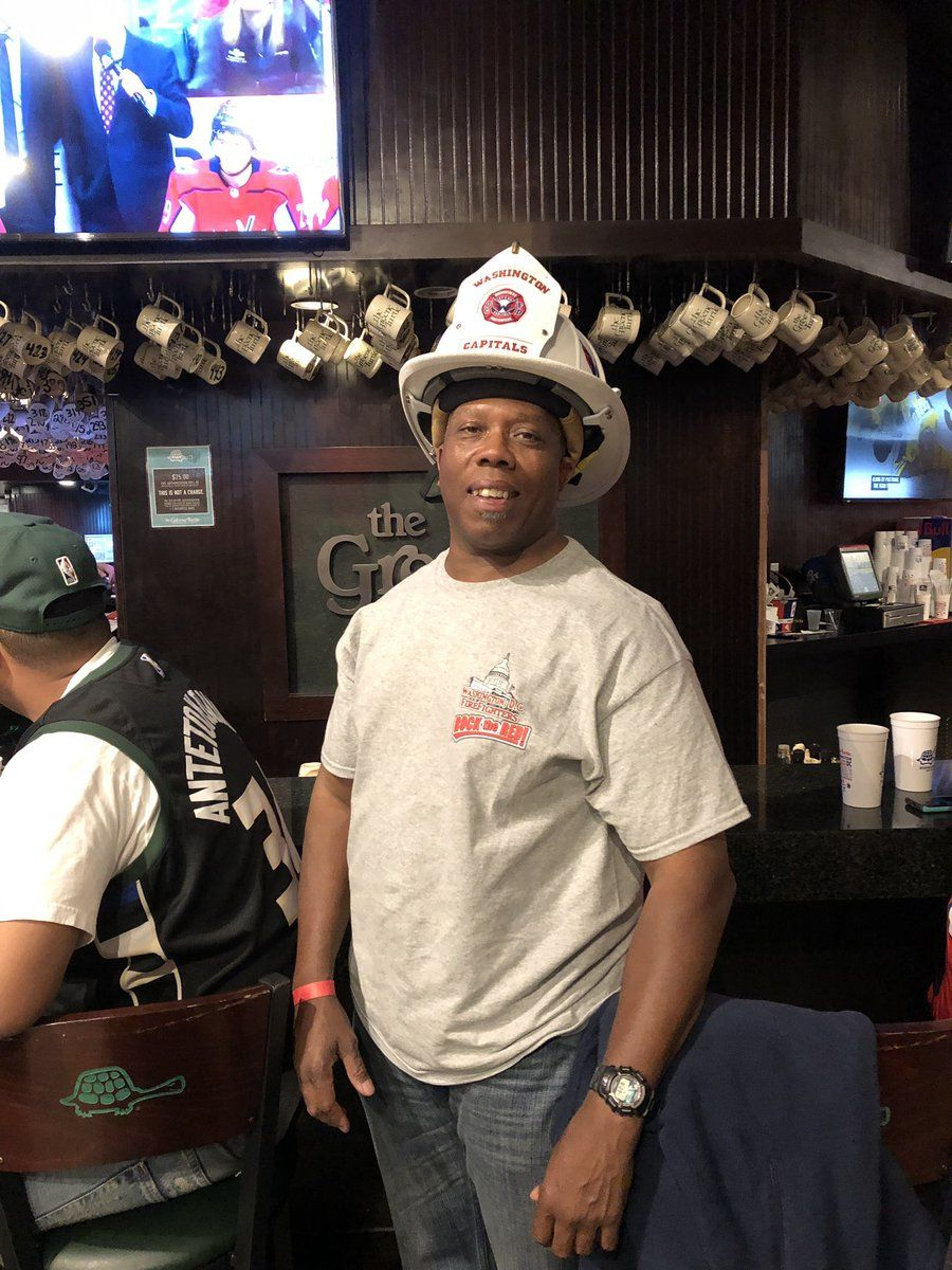 D.C. Fire and EMS Engine 5 Captain Robert Washington watching the game at the Green Turtle. His helmet salutes the fire department and the Caps. (WTOP/Mike Murillo)