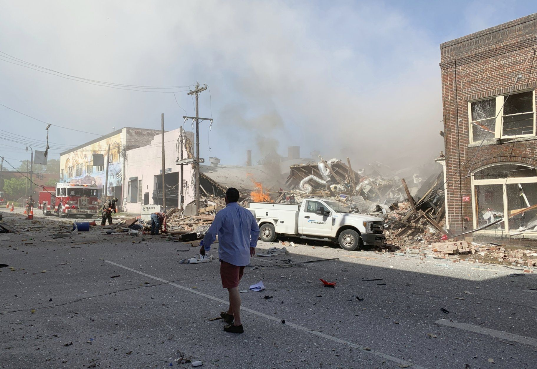 In this photo released by Jim Rogalski, firefighters help injured people after a building exploded, Wednesday, April 10, 2019, in Durham, N.C. (Jim Rogalski via AP)