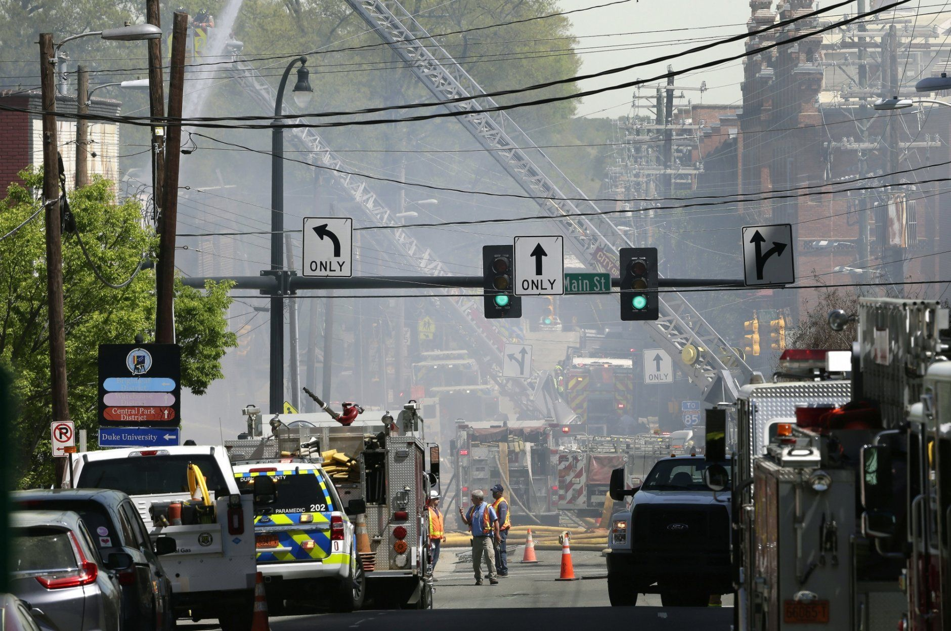Firefighters and emergency personnel work the scene of an explosion and building fire in downtown Durham, N.C., Wednesday, April 10, 2019. (AP Photo/Gerry Broome)