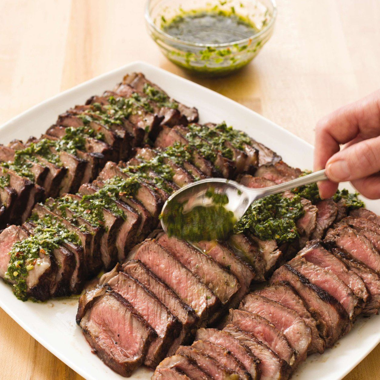 """This undated photo provided by America's Test Kitchen in April 2019 shows Argentine Steaks with Chimichurri Sauce in Brookline, Mass. This recipe appears in the cookbook """"Vegetables Illustrated."""" (Carl Tremblay/America's Test Kitchen via AP)"""