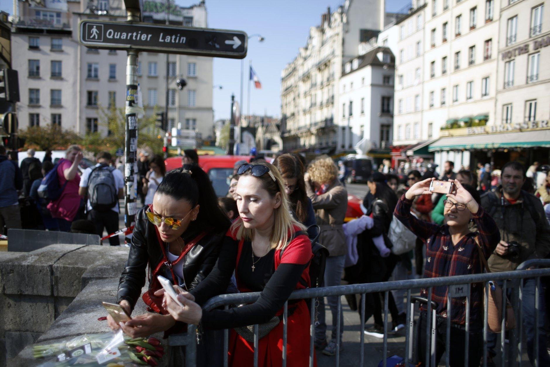 People take snapshot of flowers in front of Notre Dame cathedral, in Paris, Friday, April 19, 2019. Rebuilding Notre Dame, the 800-year-old Paris cathedral devastated by fire this week, will cost billions of dollars as architects, historians and artisans work to preserve the medieval landmark. (AP Photo/Thibault Camus)