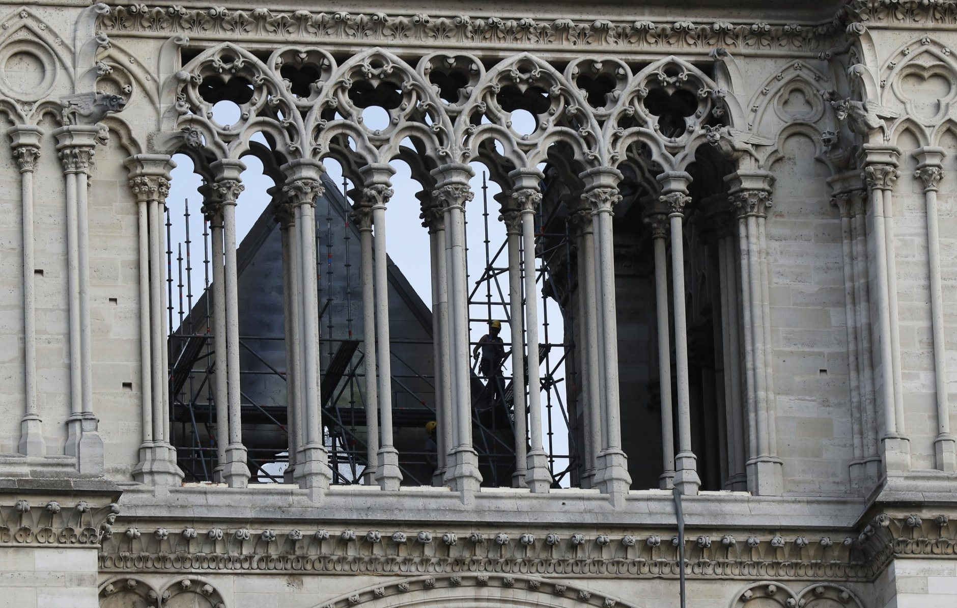 A man works at Notre Dame cathedral Thursday, April 18, 2019 in Paris. France paid a daylong tribute Thursday to the Paris firefighters who saved Notre Dame Cathedral from collapse, while construction workers rushed to secure an area above one of the church's famed rose-shaped windows and other vulnerable sections of the fire-damaged landmark. (AP Photo/Michel Euler, Pool)