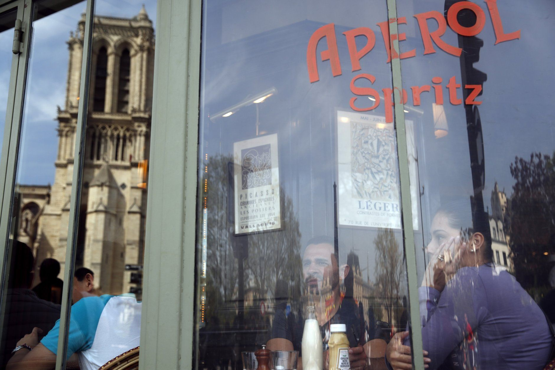 People eat at a cafe with the Notre Dame Cathedral reflected in the window in Paris, Thursday, April 18, 2019. Nearly $1 billion has already poured in from ordinary worshippers and high-powered magnates around the world to restore Notre Dame Cathedral in Paris after a massive fire. (AP Photo/Christophe Ena)