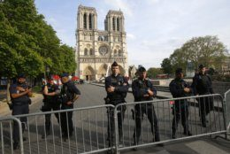 Police officer stand behind the security barriers in front of Notre Dame cathedral Thursday, April 18, 2019 in Paris. France paid a daylong tribute Thursday to the Paris firefighters who saved Notre Dame Cathedral from collapse, while construction workers rushed to secure an area above one of the church's famed rose-shaped windows and other vulnerable sections of the fire-damaged landmark. (AP Photo/Michel Euler, Pool)