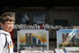 A boy walks by artwork of the Notre Dame Cathedral at a venders stall on the Left Bank in Paris, Thursday, April 18, 2019. Nearly $1 billion has already poured in from ordinary worshippers and high-powered magnates around the world to restore Notre Dame Cathedral in Paris after a massive fire. (AP Photo/Christophe Ena)