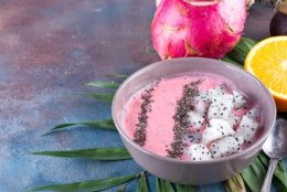 Raspberries red or pink smoothie bowls topped with fresh pitaya and chia seeds on palm leaf on stone background, copy space