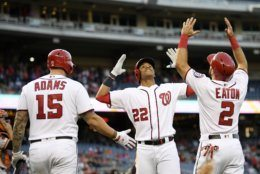 Washington Nationals' Juan Soto celebrates his two-run home run with Adam Eaton (2) and Matt Adams (15) during the first inning of the team's baseball game against the San Francisco Giants, Wednesday, April 17, 2019, in Washington. (AP Photo/Nick Wass)