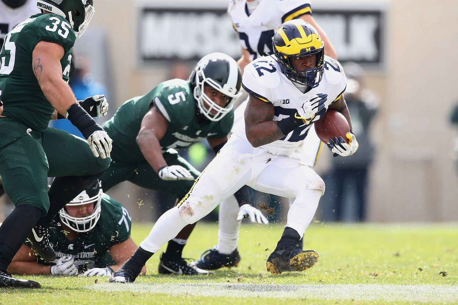 EAST LANSING, MI - OCTOBER 20: Karan Higdon #22 of the Michigan Wolverines escapes the tackle of Andrew Dowell #5 of the Michigan State Spartans during a second quarter run at Spartan Stadium on October 20, 2018 in East Lansing, Michigan. (Photo by Gregory Shamus/Getty Images)