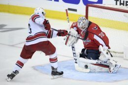 Washington Capitals goaltender Braden Holtby (70) stops the puck against Carolina Hurricanes left wing Brock McGinn (23) during the third period of Game 2 of an NHL hockey first-round playoff series, Saturday, April 13, 2019, in Washington. (AP Photo/Nick Wass)