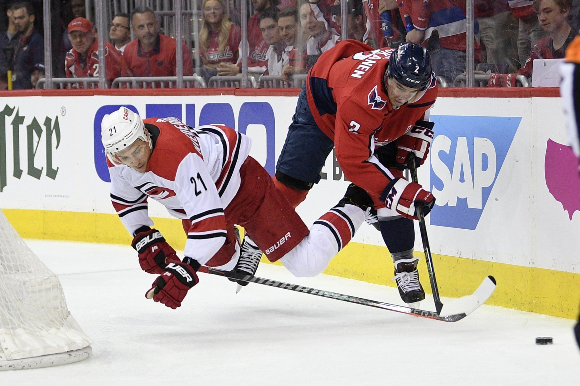 Carolina Hurricanes right wing Nino Niederreiter (21) falls to the ice next to Washington Capitals defenseman Matt Niskanen (2) during the first period of Game 2 of an NHL hockey first-round playoff series, Saturday, April 13, 2019, in Washington. (AP Photo/Nick Wass)