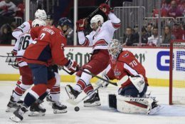 Carolina Hurricanes center Jordan Staal, center, battles for the puck against Washington Capitals goaltender Braden Holtby (70) and defenseman Matt Niskanen (2) during the first period of Game 7 of an NHL hockey first-round playoff series, Wednesday, April 24, 2019, in Washington. Also seen is Hurricanes left wing Teuvo Teravainen (86).(AP Photo/Nick Wass)