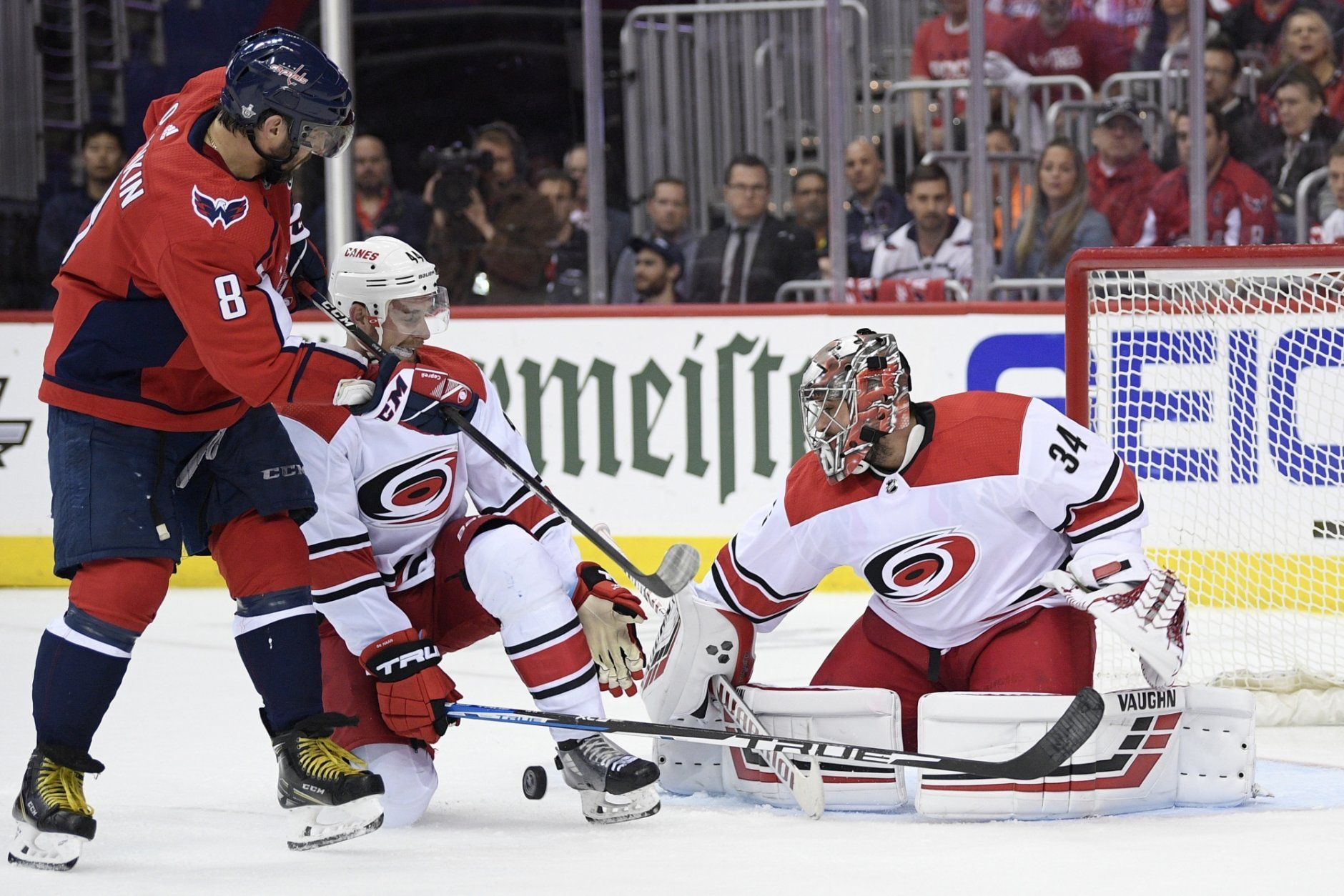 Washington Capitals left wing Alex Ovechkin (8), of Russia, battles for the puck against Carolina Hurricanes defenseman Calvin de Haan (44) and goaltender Petr Mrazek (34), of the Czech Republic, during the second period of Game 7 of an NHL hockey first-round playoff series, Wednesday, April 24, 2019, in Washington. (AP Photo/Nick Wass)