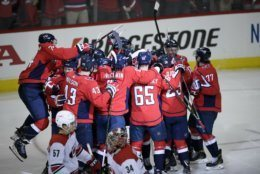The Washington Capitals celebrate after overtime of Game 2 of an NHL hockey first-round playoff series as Carolina Hurricanes defenseman Trevor van Riemsdyk (57) and goaltender Petr Mrazek (34) skate by, Saturday, April 13, 2019, in Washington. The Capitals won 4-3 in overtime. (AP Photo/Nick Wass)