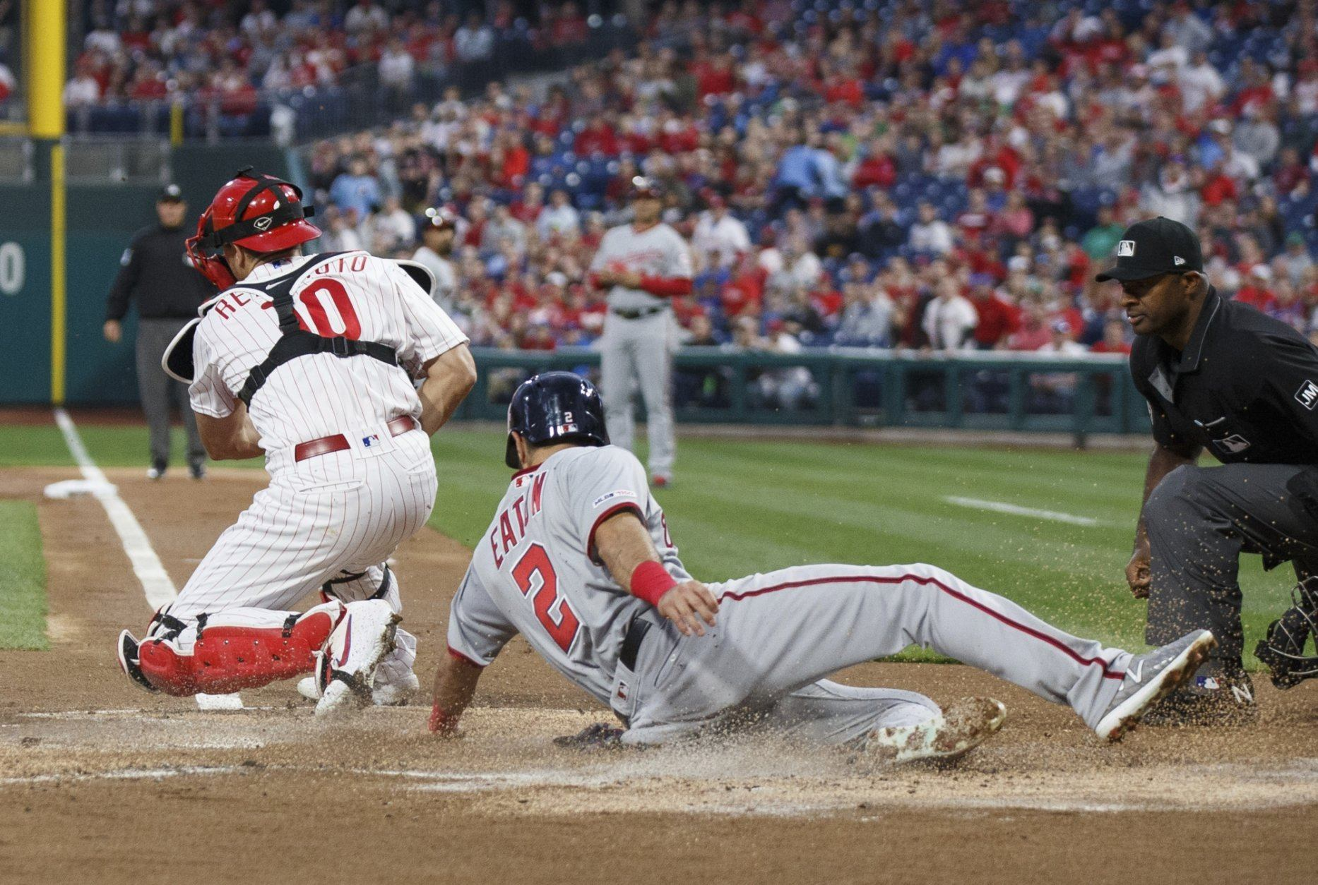 Washington Nationals' Adam Eaton scores on a sacrifice fly by Anthony Rendon as Philadelphia Phillies catcher J.T. Realmuto, left, catches the  throw during the first inning of a baseball game Tuesday, April 9, 2019, in Philadelphia. (AP Photo/Chris Szagola)