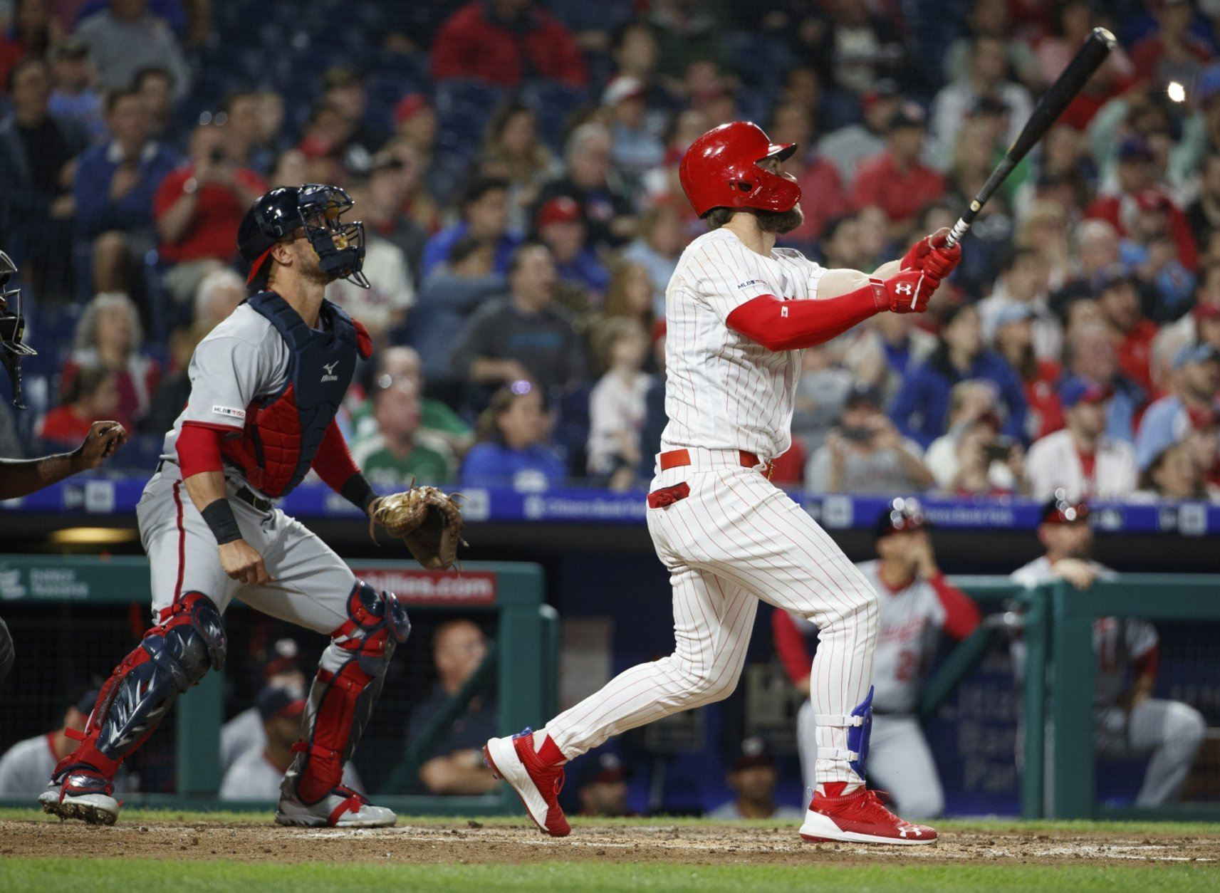 Philadelphia Phillies' Bryce Harper, right, and Washington Nationals catcher Yan Gomes watch his three-run home run during the third inning of a baseball game Tuesday, April 9, 2019, in Philadelphia. (AP Photo/Chris Szagola)