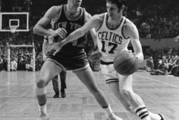 FILE - In this Thursday, April 13, 1972 file photo, Boston Celtics' John Havlicek (17) dribbles ball around New York Knicks' Bill Bradley during an NBA basketball game in Boston. The Boston Celtics say Hall of Famer John Havlicek, whose steal of Hal Green's inbounds pass in the final seconds of the 1965 Eastern Conference finals against the Philadelphia 76ers remains one of the most famous plays in NBA history, has died. The team says Havlicek died Thursday, April 25, 2019 at age 79. (AP Photo/File)