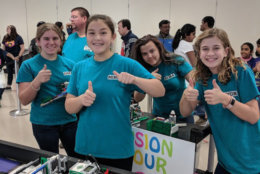 The Fusion Four team gives a thumbs-up after a successful robot practice run at the regional competition at Hayfield High School. (Courtesy Merrie Joy Hrabak)