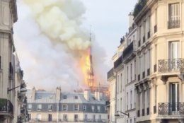 Smoke billows from the Notre Dame cathedral in the distance.