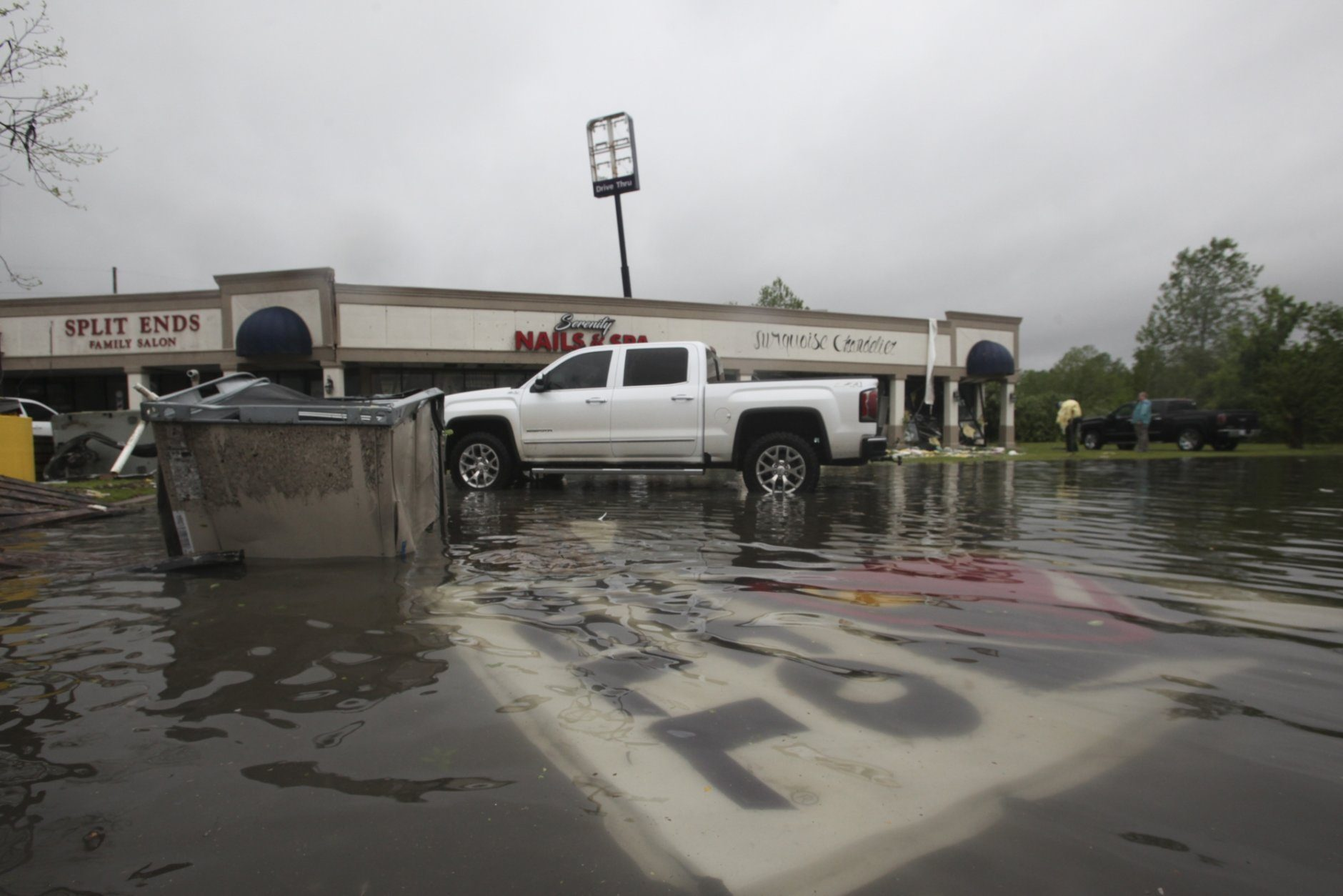 Debris is strewn in flooded water in the Pemberton Quarters strip mall following severe weather Saturday, April 13, 2019 in Vicksburg, Miss. Authorities say a possible tornado has touched down in western Mississippi, causing damage to several businesses and vehicles. John Moore, a forecaster with the National Weather Service in Jackson, says a twister was reported Saturday in the Vicksburg area of Mississippi and was indicated on radar. (Courtland Wells/The Vicksburg Post via AP)