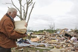 Robert Scott looks through a family bible that he just pulled out of the rubble Sunday, April 14, 2019, from his Seely Drive home outside of Hamilton, Miss. after an apparent tornado touched down Saturday night, April, 13, 2019. (AP Photo/Jim Lytle)