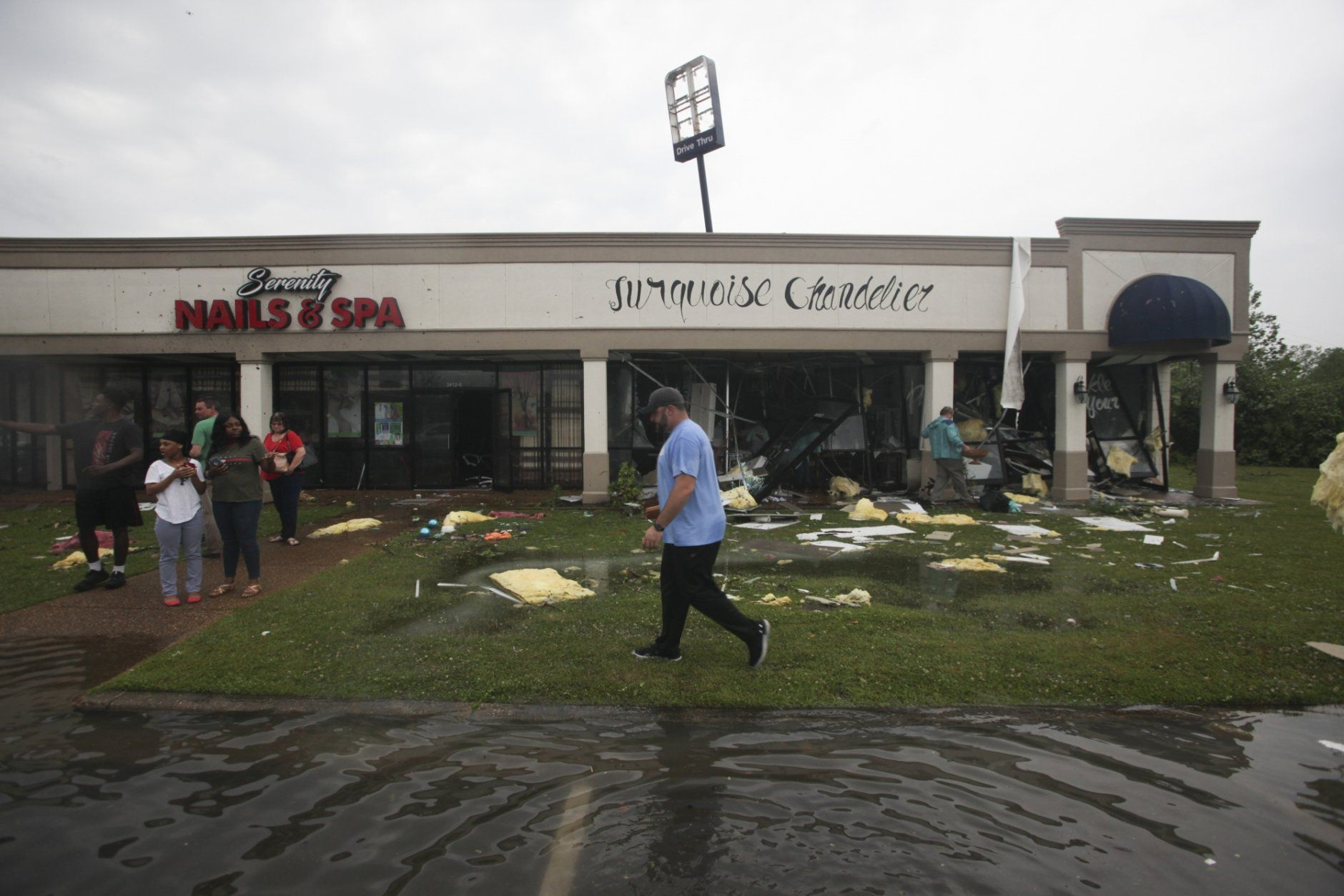 Shop owners and workers stand outside of their shops and walk through debris in the Pemberton Quarters strip mall following severe weather Saturday, April 13, 2019 in Vicksburg, Miss. Authorities say a possible tornado has touched down in western Mississippi, causing damage to several businesses and vehicles. John Moore, a forecaster with the National Weather Service in Jackson, says a twister was reported Saturday in the Vicksburg area of Mississippi and was indicated on radar. (Courtland Wells/The Vicksburg Post via AP)