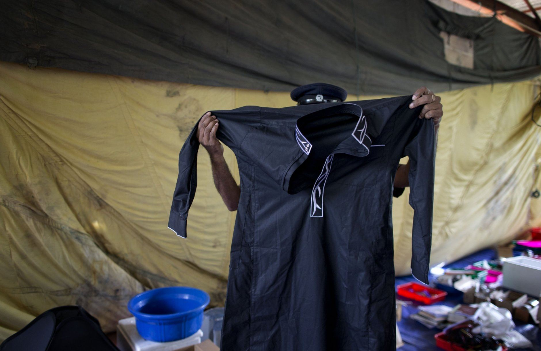 A police officer displays kandura, a traditional robe worn by some Muslim men in the Middle East, in Ampara, Sri Lanka, Sunday, April 28, 2019. Police in Ampara showed The Associated Press on Sunday the explosives, chemicals and Islamic State flag they recovered from the site of one security force raid in the region as Sri Lanka's Catholics celebrated at televised Mass in the safety of their homes. (AP Photo/Gemunu Amarasinghe)
