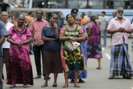 Sri Lankan Catholics pray as they attend a brief holly service standing on the road near the exploded St. Anthony's Church, marking the seventh day of the Easter Sunday attacks in Colombo, Sri Lanka, Sunday, April 28, 2019. Sri Lanka's Catholics on Sunday awoke preparing to celebrate Mass in their homes by a televised broadcast as churches across the island shut over fears of militant attacks, a week after the Islamic State-claimed Easter suicide bombings. (AP Photo/Eranga Jayawardena)