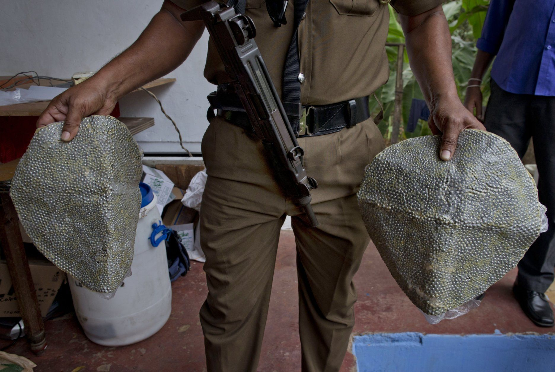 A police officer displays ball-bearings that increase the lethality of explosions in Ampara, Sri Lanka, Sunday, April 28, 2019. Police in Ampara showed The Associated Press on Sunday the explosives, chemicals and Islamic State flag they recovered from the site of one security force raid in the region as Sri Lanka's Catholics celebrated at televised Mass in the safety of their homes. (AP Photo/Gemunu Amarasinghe)