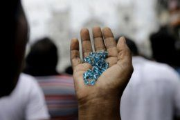 A Sri Lankan Catholic holds her rosary as she prays on a road during a brief holly mass held outside the exploded St. Anthony's Church marking the seventh day of the Easter Sunday attacks in Colombo, Sri Lanka, Sunday, April 28, 2019. Sri Lanka's Catholics on Sunday awoke preparing to celebrate Mass in their homes by a televised broadcast as churches across the island shut over fears of militant attacks, a week after the Islamic State-claimed Easter suicide bombings. (AP Photo/Eranga Jayawardena)