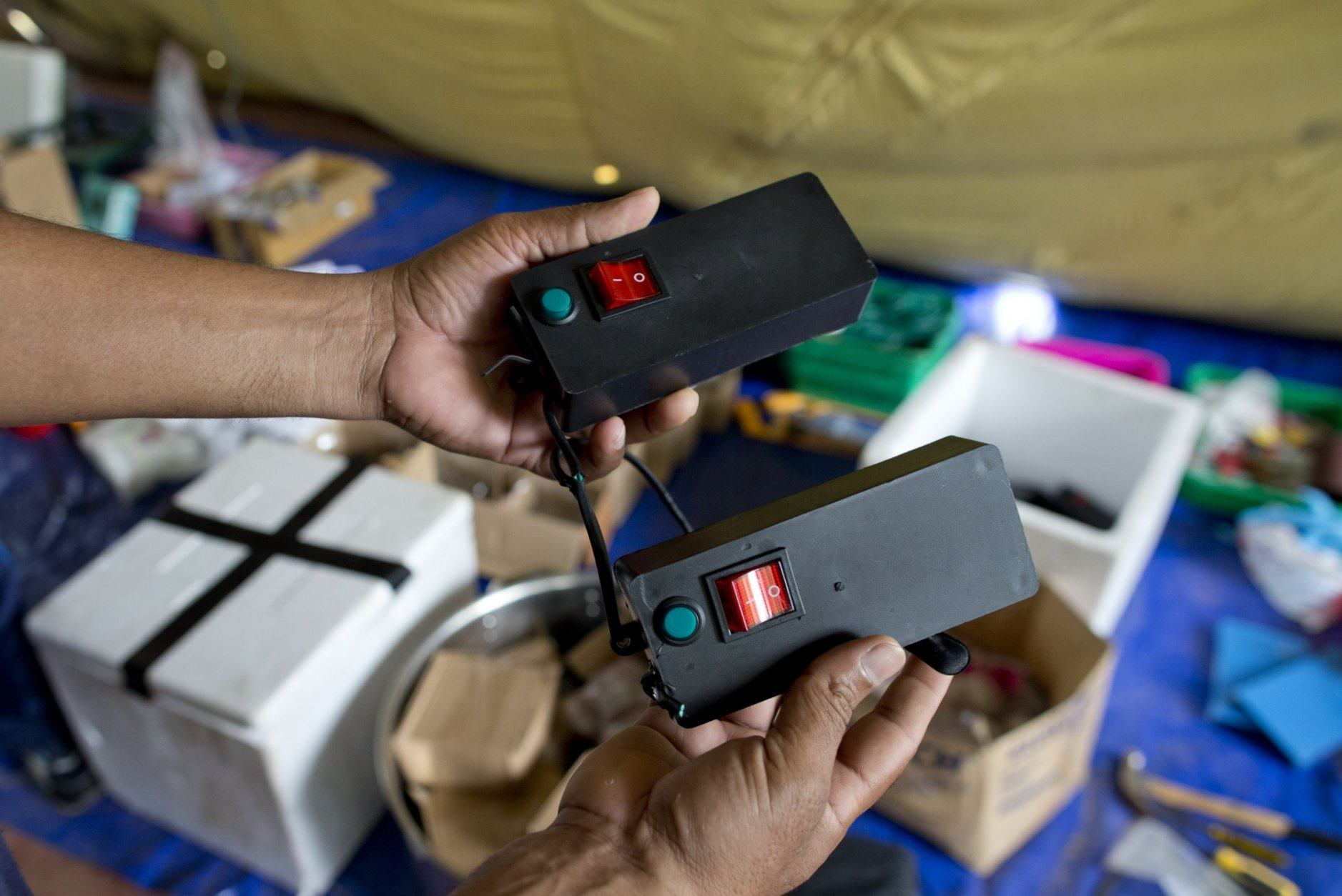 A police officer displays detonators and other bomb making materials in Ampara, Sri Lanka, Sunday, April 28, 2019. Police in Ampara showed The Associated Press on Sunday the explosives, chemicals and Islamic State flag they recovered from the site of one security force raid in the region as Sri Lanka's Catholics celebrated at televised Mass in the safety of their homes. (AP Photo/Gemunu Amarasinghe)