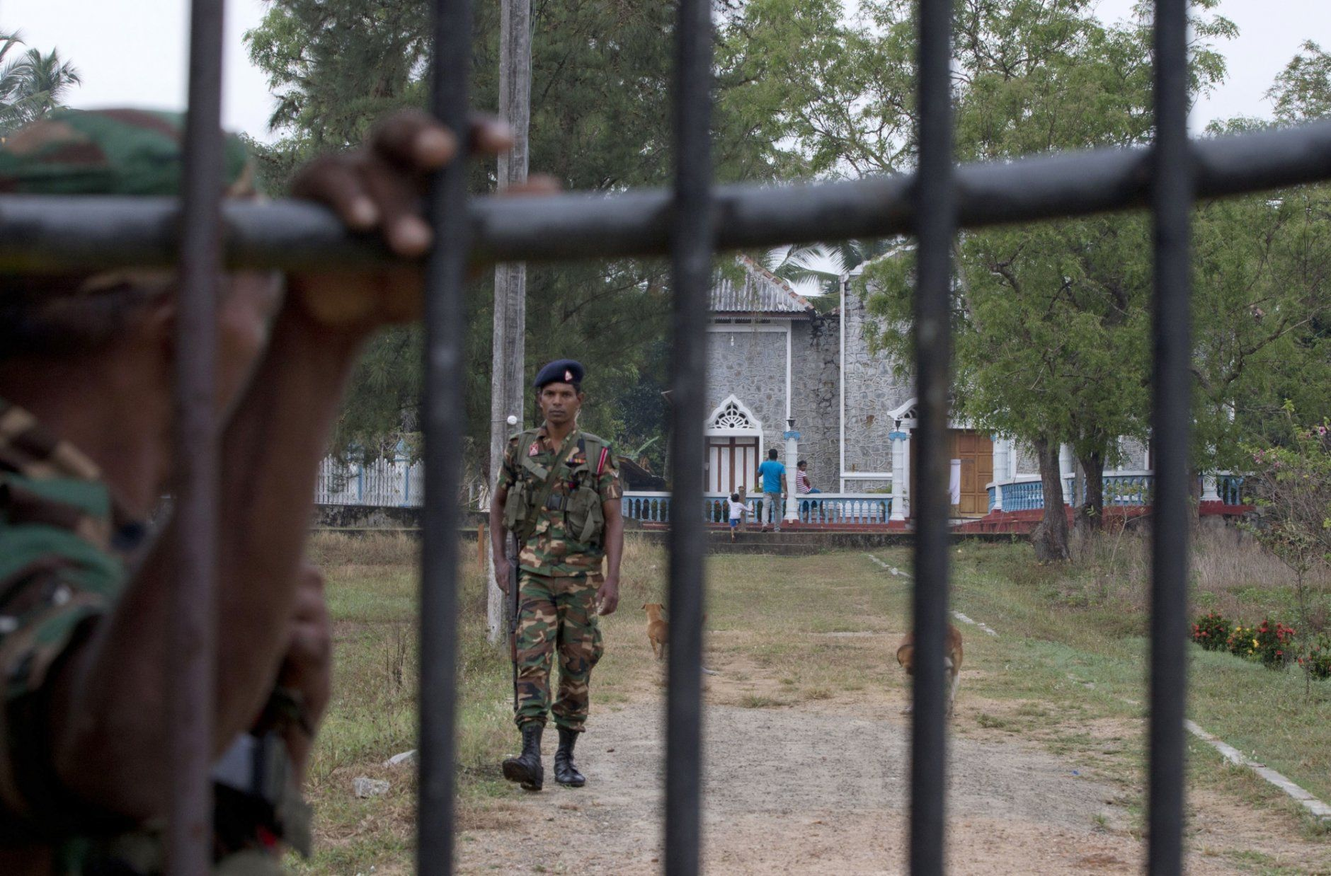 Soldiers stand guard at a church garden with a locked gate in Ampara, Sri Lanka, Sunday, April 28, 2019. Sri Lanka's Catholics on Sunday awoke preparing to celebrate Mass in their homes by a televised broadcast as churches across the island shut over fears of militant attacks, a week after the Islamic State-claimed Easter suicide bombings. (AP Photo/Gemunu Amarasinghe)