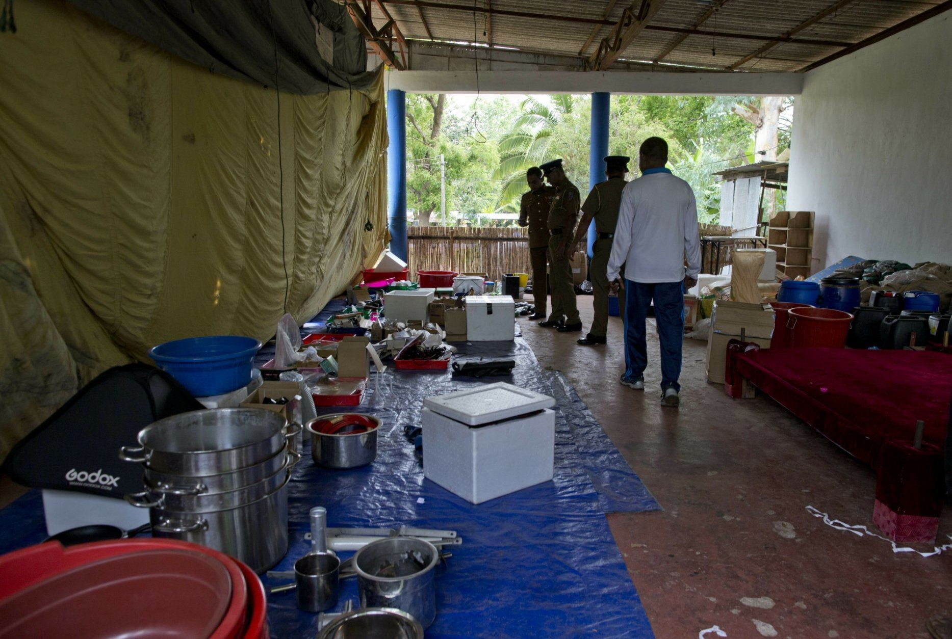 Police officers gather at outdoor stage used for storing evidence seized from militants in Ampara, Sri Lanka, Sunday, April 28, 2019. Police in Ampara showed The Associated Press on Sunday the explosives, chemicals and Islamic State flag they recovered from the site of one security force raid in the region as Sri Lanka's Catholics celebrated at televised Mass in the safety of their homes. (AP Photo/Gemunu Amarasinghe)
