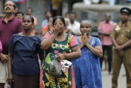 Sri Lankan Catholics pray standing on a road as they attend a brief holly service marking the seventh day of the Easter Sunday attacks near the exploded St. Anthony's Church in Colombo, Sri Lanka, Sunday, April 28, 2019. Sri Lanka's Catholics on Sunday awoke preparing to celebrate Mass in their homes by a televised broadcast as churches across the island shut over fears of militant attacks, a week after the Islamic State-claimed Easter suicide bombings. (AP Photo/Eranga Jayawardena)