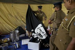 """Police officers display a flag in Arabic that reads: """"There is no god, but Allah"""" and """"Of Allah is the Prophet, Muhammad"""" in Ampara, Sri Lanka, Sunday, April 28, 2019. Police in Ampara showed The Associated Press on Sunday the explosives, chemicals and Islamic State flag they recovered from the site of one security force raid in the region as Sri Lanka's Catholics celebrated at televised Mass in the safety of their homes. (AP Photo/Gemunu Amarasinghe)"""