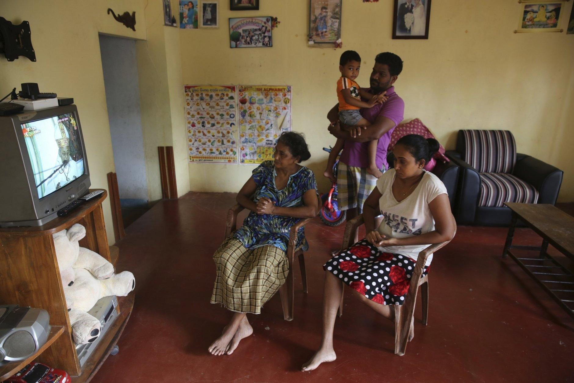 A Sri Lankan Christian catholic family watches and prays inside their home watching live transmission of Sri Lankan Archbishop Cardinal Malcolm Ranjith, in Negombo, Sri Lanka, Sunday, April 28, 2019. Sri Lanka's Catholics celebrated Sunday Mass in their homes by a televised broadcast as churches across the island nation shut over fears of militant attacks, a week after the Islamic State-claimed Easter suicide bombings killed over 250 people. (AP Photo/Manish Swarup)