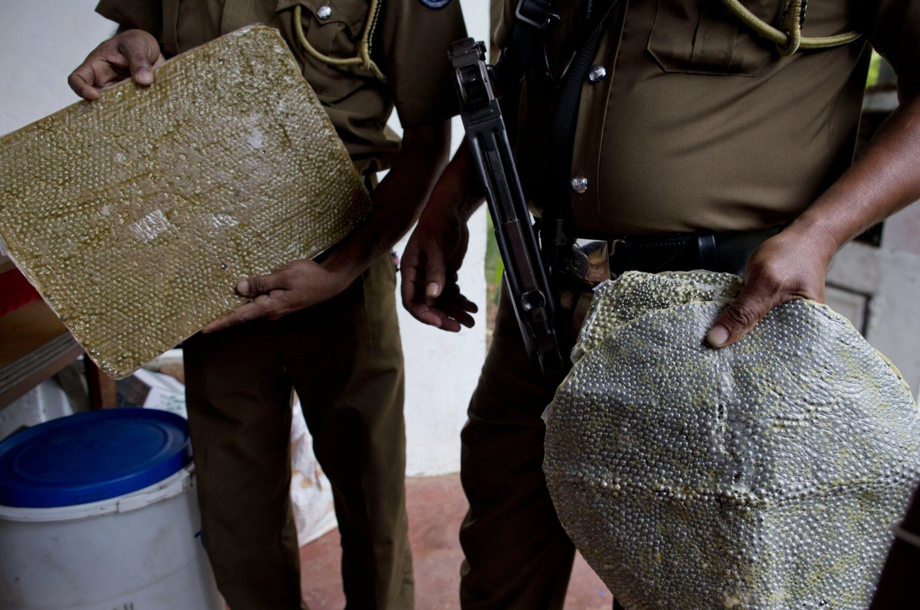 Police officers display ball-bearings that increase the lethality of explosions in Ampara, Sri Lanka, Sunday, April 28, 2019. Police in Ampara showed The Associated Press on Sunday the explosives, chemicals and Islamic State flag they recovered from the site of one security force raid in the region as Sri Lanka's Catholics celebrated at televised Mass in the safety of their homes. (AP Photo/Gemunu Amarasinghe)