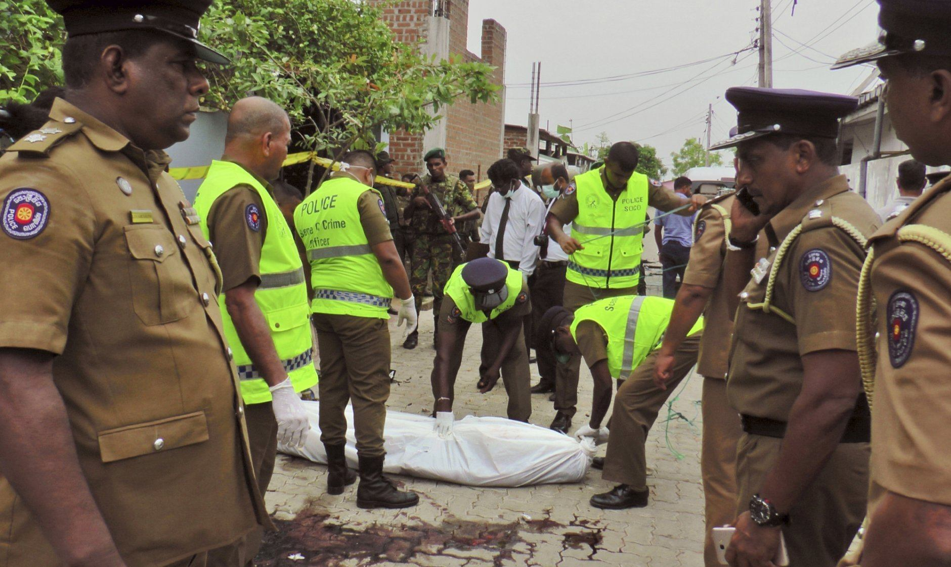 Sri Lankan policemen cover the body of a alleged terrorist after he was shot during a gun-battle in Kalmunai, in eastern Sri Lanka, Saturday, April 27, 2019. Militants linked to Easter suicide bombings opened fire and set off explosives during a raid by Sri Lankan security forces on a house in the country's east, leaving behind 15 bodies, including six children. (AP Photo/Achala Upendra)